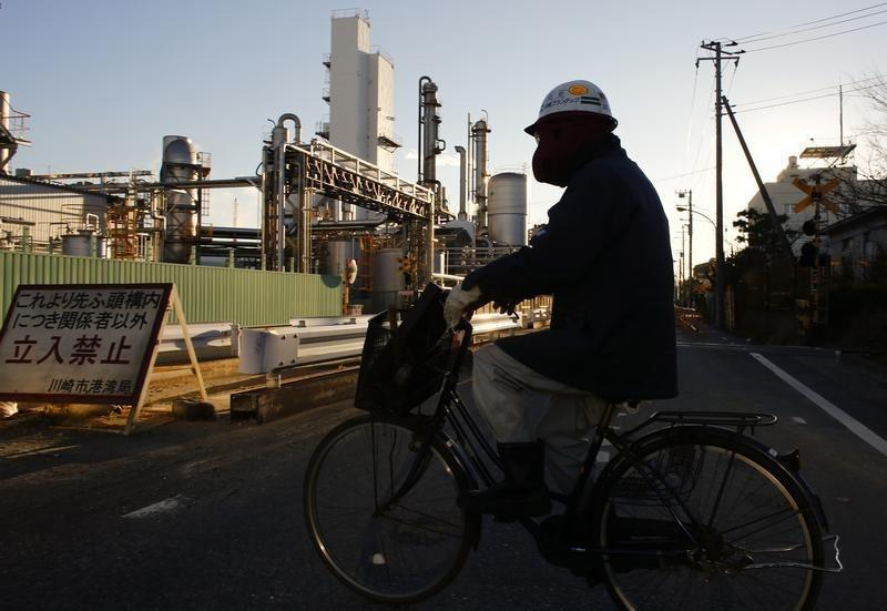 A worker cycles past a petro-industrial complex in Kawasaki near Tokyo