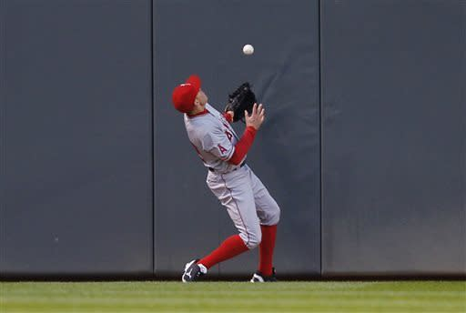 Los Angeles Angels center fielder Peter Bourjos bobbles the ball after Minnesota Twins' Joe Mauer hits a double during the first inning of a baseball game Monday, April 15, 2013, in Minneapolis. (AP Photo/Genevieve Ross)