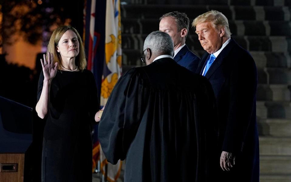 Amy Coney Barrett takes the oath beside Donald Trump at the White House - AP