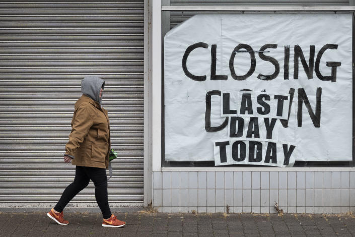 A woman walks passed a closed-down shop on June 10, 2020 in Aberdare, United Kingdom. Photo: Matthew Horwood/Getty Images