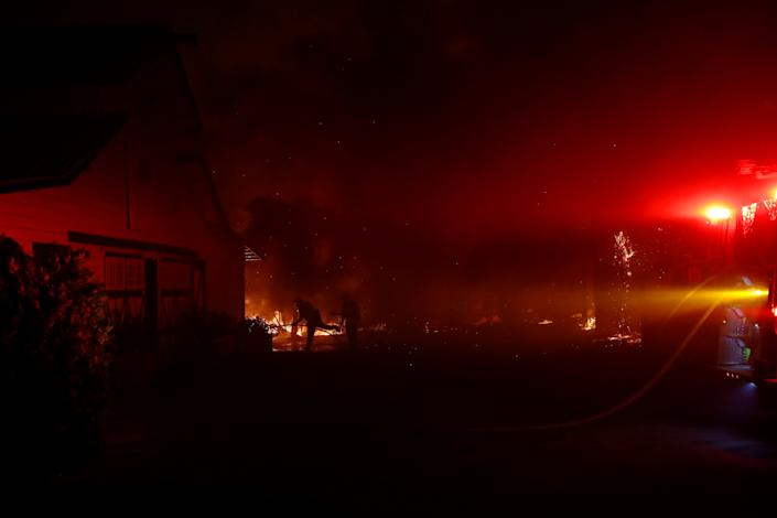 Firefighters work to contain a burning structure during the wind-driven Kincade Fire in Windsor, California, Oct. 27, 2019. (Photo: Stephen Lam/Reuters)