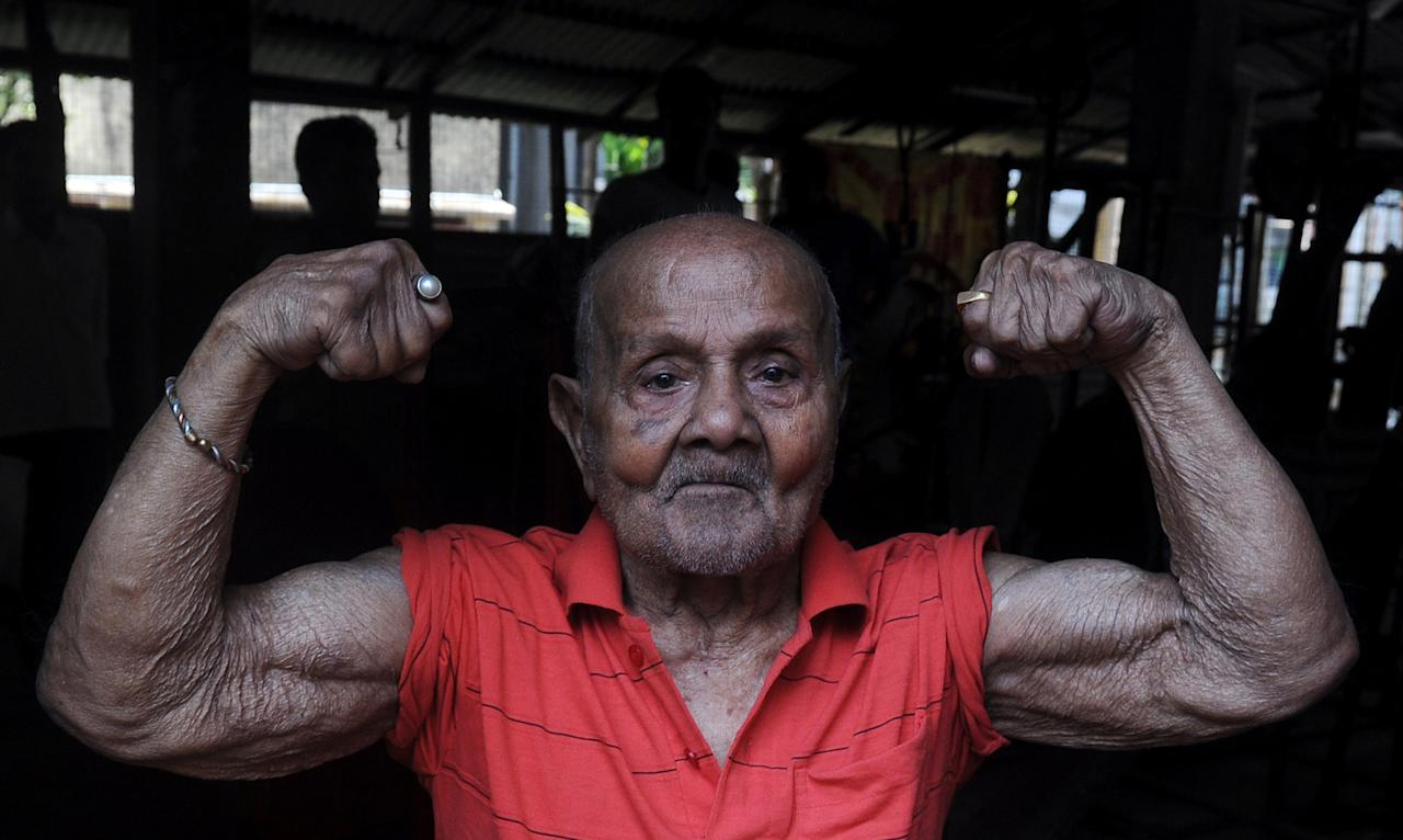 "Indian body builder Manohar Aich (C) shows his muscles on the eve of his 100th birthday, in a gymnasium in Kolkata on March 16, 2012. Aich, born on March 17, 1913, won the 1952 Mr. Universe Group III championship and is also a three time Asian Games gold medalist in body building. Being only 4 feet 11 inches (1.50 m) tall, he also goes by the nickname ""Pocket Hercules"". AFP PHOTO/Dibyangshu SARKAR (Photo credit should read DIBYANGSHU SARKAR/AFP/Getty Images)"