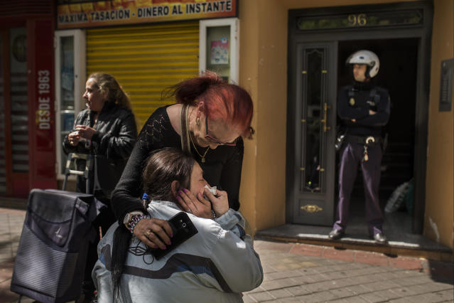 <p>A police officer stands guard as Maria Luisa Montiel, 47, cries during her eviction in Madrid, April 28, 2015. (AP Photo/Andres Kudacki) </p>
