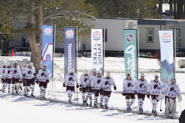 Members of the Colorado Avalanche walk to the rink to play the Vegas Golden Knights in the Lake Tahoe Outdoor NHL hockey game at Stateline, Nev., Saturday, Feb. 20, 2021. (AP Photo/Rich Pedroncelli))