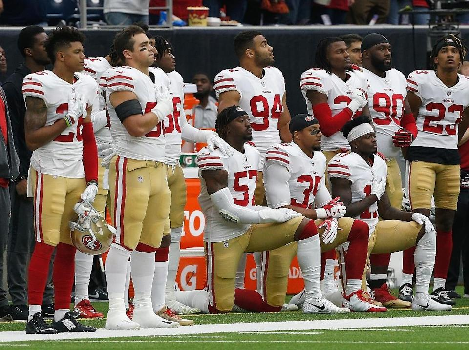 San Francisco 49ers players take a knee during the national anthem in a game in 2017. (AFP Photo/Bob Levey)