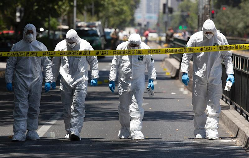 Police bomb squad personnel inspect the scene after a blast at a bus stop injured at least four people in downtown Santiago