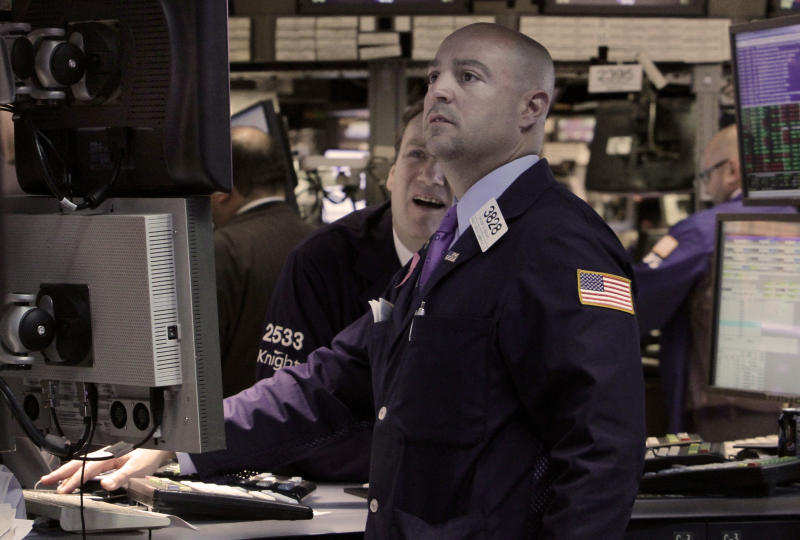 In an April 16, 2012 photo specialists Patrick King, left, and Frank Babino work on the floor of the New York Stock Exchange.  Wall Street appeared headed for a lower opening Monday April 23, 2011, with Dow Jones industrial futures down 0.9 percent  and S&P 500 futures 1 percent lower  (AP Photo/Richard Drew)