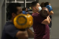 FILE - In this Nov. 24, 2020, file photo, Juan Avellan, center, and others wear masks while working out in an indoor class at a Hit Fit SF gym amid the coronavirus outbreak in San Francisco. Health officials in San Francisco and six other Bay Area counties announced Monday, Aug. 2, 2021 that they are reinstating a mask mandate for all indoor setting as COVID-19 infections surge because of the highly contagious delta variant. (AP Photo/Jeff Chiu, File)
