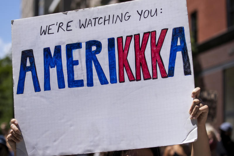 "MANHATTAN, NY - JUNE 12: A protester holds a homemade sign that says, ""We're Watching You Amerikka"" with the letters of the kkk in red during a protest with hundreds of people that marched in the streets to Gracie Mansion. This was part of the Black Womxn's Empowerment March that started at Trump Tower and marched to Gracie Mansion. Protesters continue taking to the streets across America and around the world after the killing of George Floyd at the hands of a white police officer Derek Chauvin that was kneeling on his neck during for eight minutes, was caught on video and went viral. During his arrest as Floyd pleaded, ""I Can't Breathe"". The protest are attempting to give a voice to the need for human rights for African American's and to stop police brutality against people of color. They are also protesting deep-seated racism in America. Many people were wearing masks and observing social distancing due to the coronavirus pandemic. Photographed in the Manhattan Borough of New York on June 12, 2020, USA. (Photo by Ira L. Black/Corbis via Getty Images)"