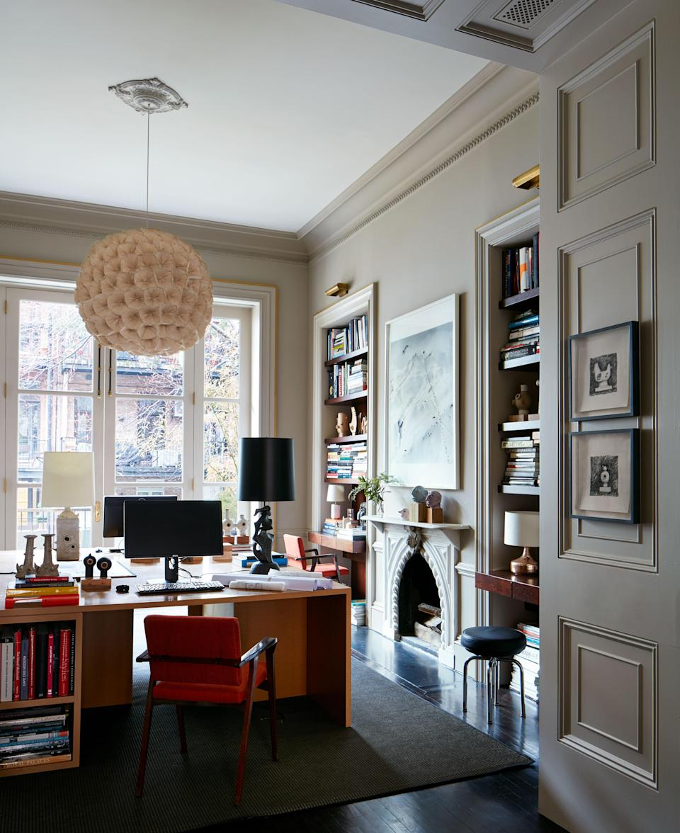 This large space, painted in Benjamin Moore Ashen Tan, was immediately transformed into Otero's home office for the interior design studio and is retained as a place to draw, sketch, and prepare his ceramic works. The pendant light is made up of dried poppy flowers and was purchased when he lived in Hong Kong. The 1950s rosewood chairs were reupholstered in red-orange linen from Gaston y Daniela at Kravet.