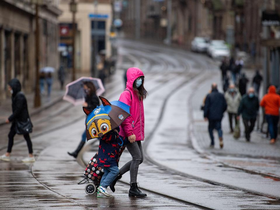 People hold umbrellas and don raincoats in the rain in Nottingham (PA)