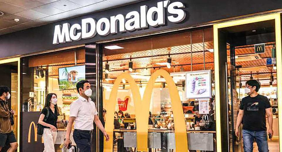 People wearing face masks as a preventive measure against the spread of coronavirus walk past a McDonald's restaurant at Seoul Station in Seoul.