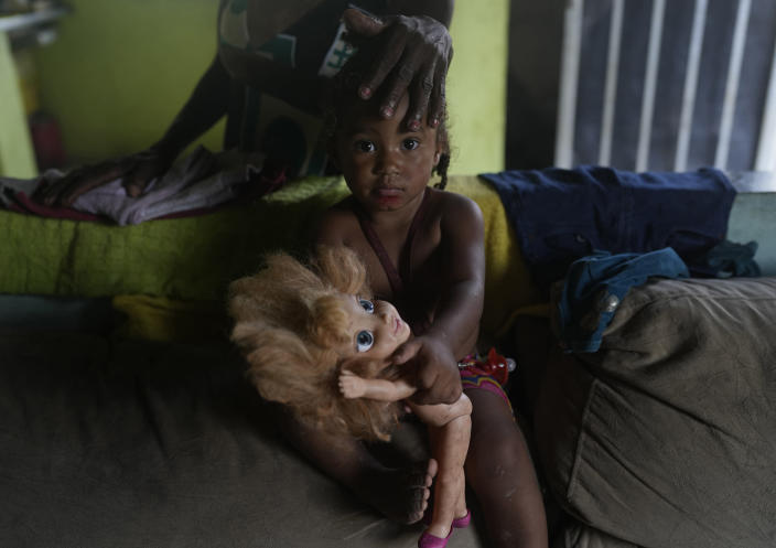 Eloa, 2, looks at the camera as her grandmother Lady Laurentino, 74, caresses her, at their home in the Jardim Gramacho favela of Rio de Janeiro, Brazil, Monday, Oct. 4, 2021. After the recent surge in gas prices, Laurentino says she is cooking with wood these days because she doesn't have money to buy a new gas cylinder. (AP Photo/Silvia Izquierdo)