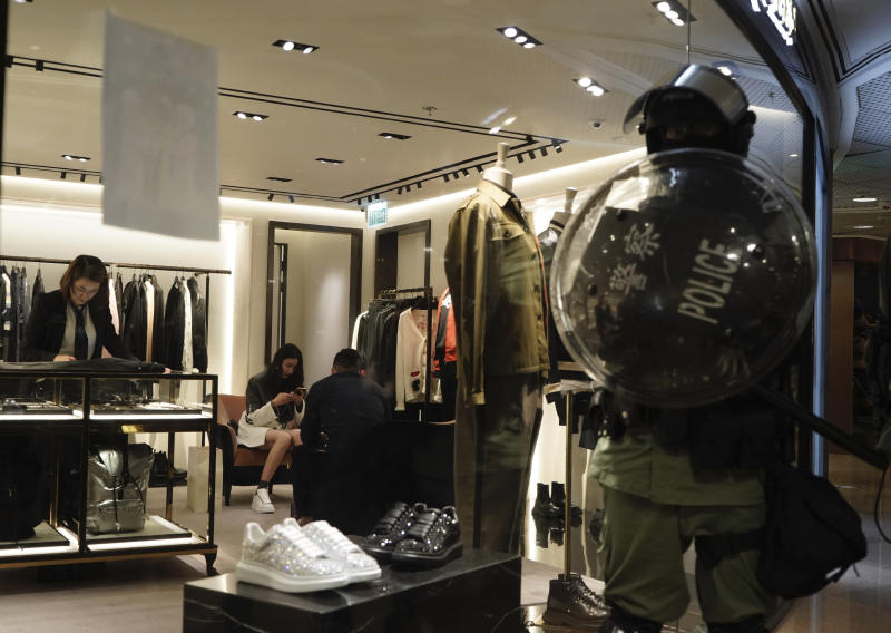 Shoppers continue to patronize retail stores as a riot police stand by in a mall on Christmas Eve in Hong Kong on Tuesday, Dec. 24, 2019. More than six months of protests have beset the city with frequent confrontations between protesters and police. (AP Photo/Kin Cheung)