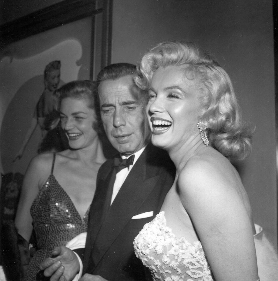 <p>Marilyn laughed with Humphrey Bogart and Lauren Bacall at the premiere of <em>How to Marry a Millionaire</em>. </p>