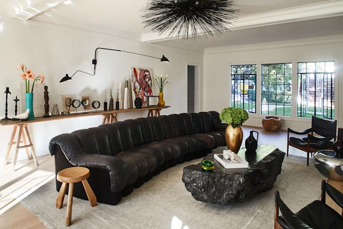 "<div class=""caption""> A curved de Sede black leather vintage sofa dominates the living room, and a sea urchin–like <a href=""https://jeandemerry.com/"" rel=""nofollow noopener"" target=""_blank"" data-ylk=""slk:Jean de Merry"" class=""link rapid-noclick-resp"">Jean de Merry</a> Spike chandelier looks down on the space. Behind the sitting area, Serge Mouille lighting hangs over a table of vintage objects and Robert Kuo vases. </div>"