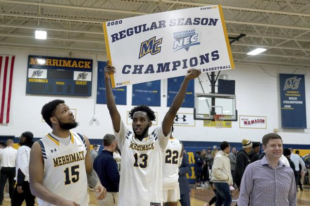 In this Thursday, Feb. 27, 2020 photo, Merrimack College guard Jaleel Lord, center, holds a sign with teammate Idris Joyner, left, and coach Joe Gallo, right, after defeating Central Connecticut in an NCAA college basketball game to claim a portion of the regular season championship in the Northeast Conference in North Andover, Mass. The Warriors have been one of the biggest surprises in college basketball, winning more games than any other first-year Division I program in history. (AP Photo/Mary Schwalm)