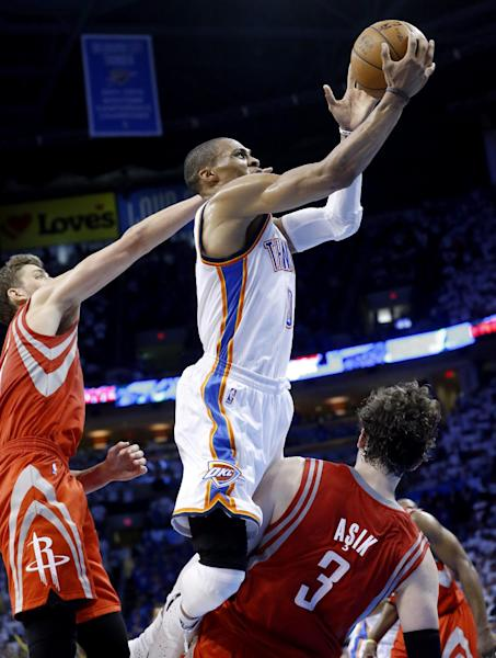 Oklahoma City Thunder guard Russell Westbrook (0) is fouled by Houston Rockets center Omer Asik as he shoots in the fourth quarter of Game 2 of their first-round NBA basketball playoff series in Oklahoma City, Wednesday, April 24, 2013. Oklahoma City won 105-102. (AP Photo/Sue Ogrocki)