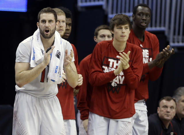 Louisville guard/forward Luke Hancock, left, cheers his team during the second half in a third-round game in the NCAA college basketball tournament against Saint Louis, Saturday, March 22, 2014, in Orlando, Fla. (AP Photo/John Raoux)
