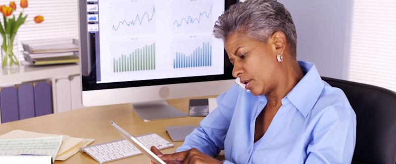 Senior black businesswoman talking on smartphone and using tablet