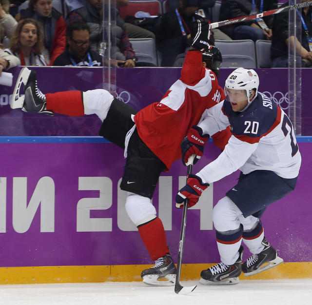 Canada forward Patrick Sharp, left, collides with USA defenseman during the first period of a men's semifinal ice hockey game at the 2014 Winter Olympics, Friday, Feb. 21, 2014, in Sochi, Russia. (AP Photo/Petr David Josek)
