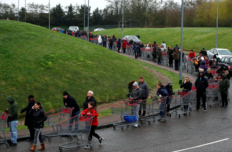 Shoppers queue round the block to get into a Watford branch of Costco. (Reuters)