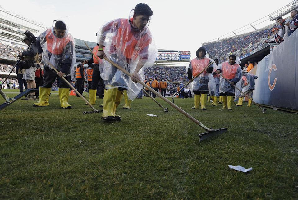 Soldier Field's ground crew prepares the field to resume play after a severe storm blew through the area and suspended play during the first half of an NFL football game between the Chicago Bears and Baltimore Ravens, Sunday, Nov. 17, 2013, in Chicago. (AP Photo/Nam Y. Huh)
