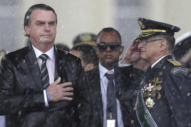 In this April 17, 2019 photo, Brazil's President Jair Bolsonaro puts his hand over his heart as Army Commander Edson Leal Pujol salutes during the playing of the national anthem during a ceremony marking Army Day, in Brasilia, Brazil. Brazil's Army Day is officially on Friday, April 19. (AP Photo/Eraldo Peres)