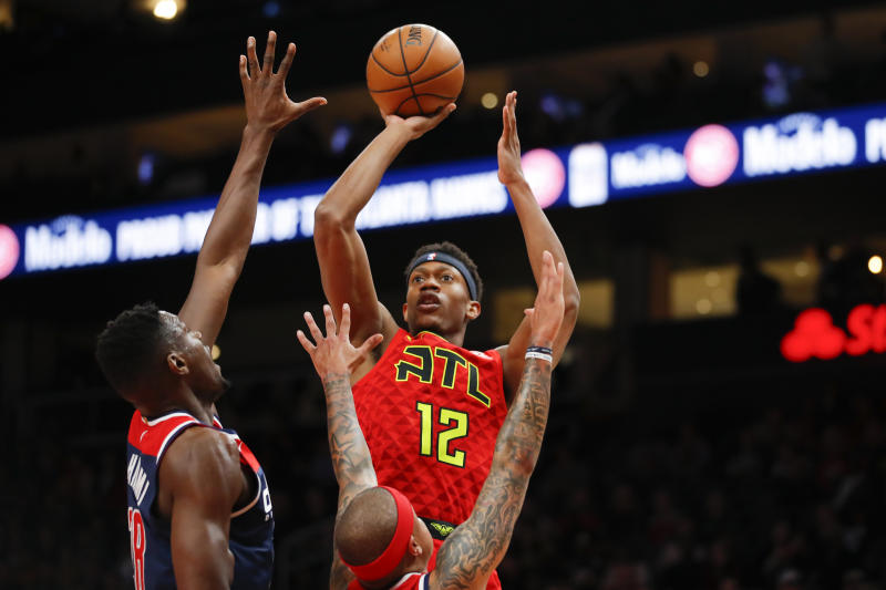 CORRECTS TO DE'ANDRE HUNTER, NOT GRAHAM - Atlanta Hawks forward De'Andre Hunter (12) shoots during the first half of an NBA basketball game against the Washington Wizards, Sunday, Jan. 26, 2020, in Atlanta. (AP Photo/Todd Kirkland)