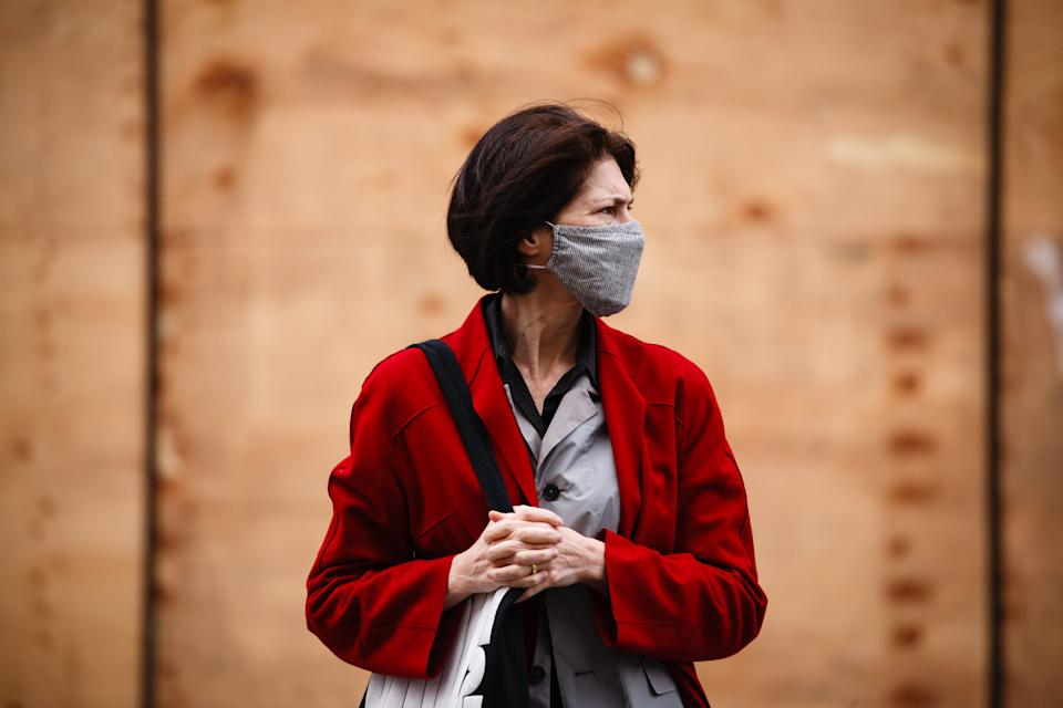 A woman wearing a face mask waits at a pedestrian crossing on Regent Street in London, England, on November 6, 2020. England yesterday began its second national coronavirus lockdown, announced by British Prime Minister Boris Johnson last Saturday, citing fears that covid-19 again threatened to overwhelm the National Health Service (NHS). Pubs, bars, restaurants and non-essential shops are all required to be closed until the currently scheduled end date of December 2. People have meanwhile been asked to stay home as much as possible, although schools and other educational institutions are this time being being kept open and the streets of central London today were markedly busier than the early days of the first lockdown in the spring. (Photo by David Cliff/NurPhoto via Getty Images)