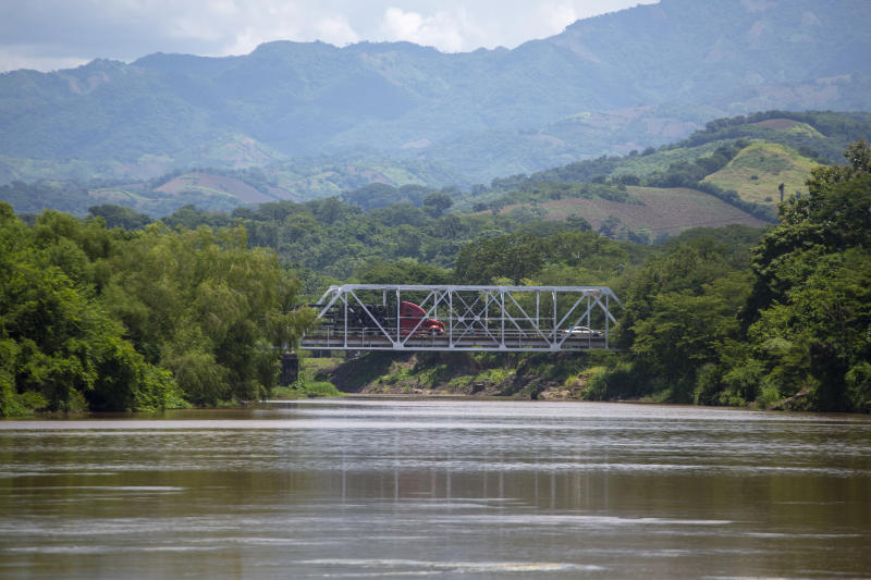 A truck crosses a bridge over La Paz River, from Guatemala to El Salvador, seen from La Hachadura, El Salvador, Thursday, Sept. 12, 2019. El Salvador's deployment of a new border patrol at this site is part of an agreement between the Salvadoran government and acting U.S. Homeland Security Secretary Kevin McAleenan to slow the flow of migrants trying to reach the United States. (AP Photo/Moises Castillo)