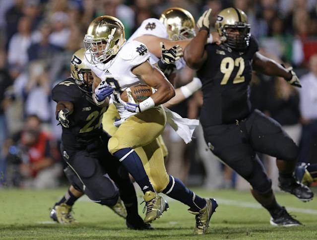 Notre Dame running back Amir Carlisle, center, picks up yards as he gets past Purdue defensive tackle Ryan Watson (92) and cornerback Ricardo Allen during the first half of an NCAA college football game in West Lafayette, Ind., Saturday, Sept. 14, 2013. (AP Photo/Michael Conroy)