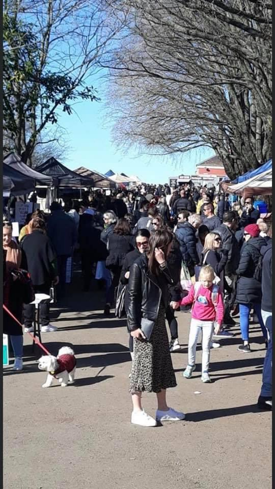 The photo shows a crowd of adults, children and even dogs at a busy small-town market in Victoria.