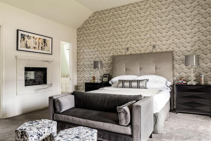 The main bedroom doubles as a hangout for the grown-ups of the home, so it's generous enough to hold a bedside fireplace plus a sitting area with a television. The geometric wallpaper provides the black-and-white anchor that has become Lucinda Loya's signature.
