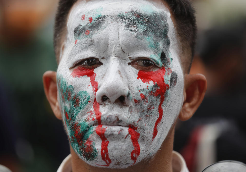 An anti-government protester paints his face blood crying during a protest near Democracy Monument in Bangkok, Thailand, Wednesday, Oct. 14, 2020. Thai activists hope to keep up the momentum in their campaign for democratic change with a third major rally in Bangkok on Wednesday. (AP Photo/Sakchai Lalit)