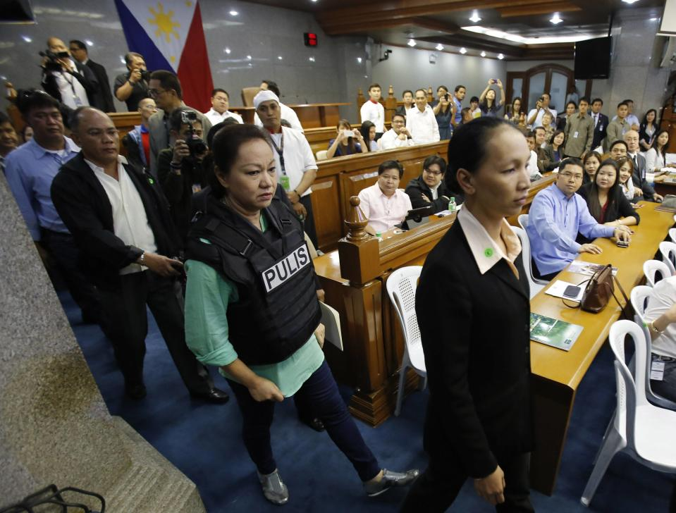 Janet Lim Napoles (2nd R), wearing a bullet proof vest, is escorted by police agents upon arriving at the Senate to testify at a public inquiry in Manila November 7, 2013. Napoles, the wife of a former Marine major, has been accused by the Department of Justice of setting up fake non-government organisations that since 2007 received lawmakers' pork barrel funds and then routed the money back to them. The whistleblower, a former associate of Napoles, testified to the Senate in a public hearing that the businesswoman received so much cash she would stash it in the bathtub of her luxury Manila home. Napoles was arrested and charged with plunder in September, along with 30 others including three senators and five former congress members. Before her arrest, Napoles denied involvement in the scheme and said her wealth came from her family's investments in coal mining in Indonesia. REUTERS/Romeo Ranoco (PHILIPPINES - Tags: POLITICS CRIME LAW)