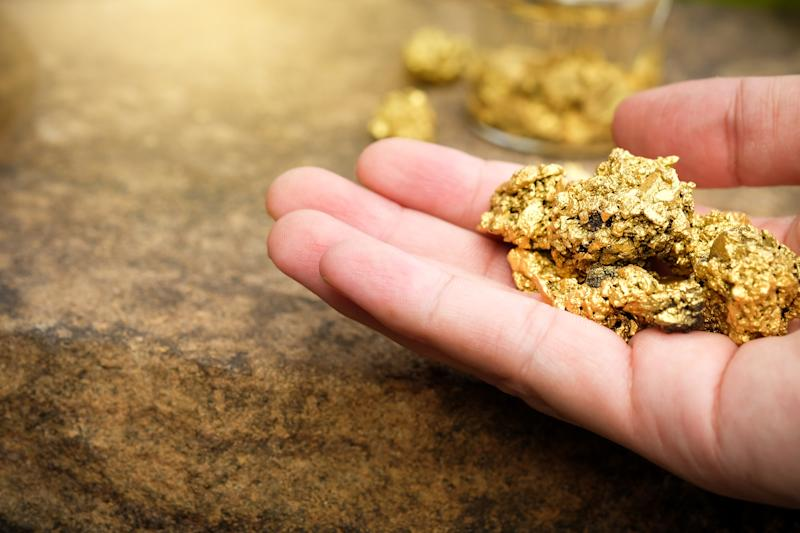 A hand holding gold pieces