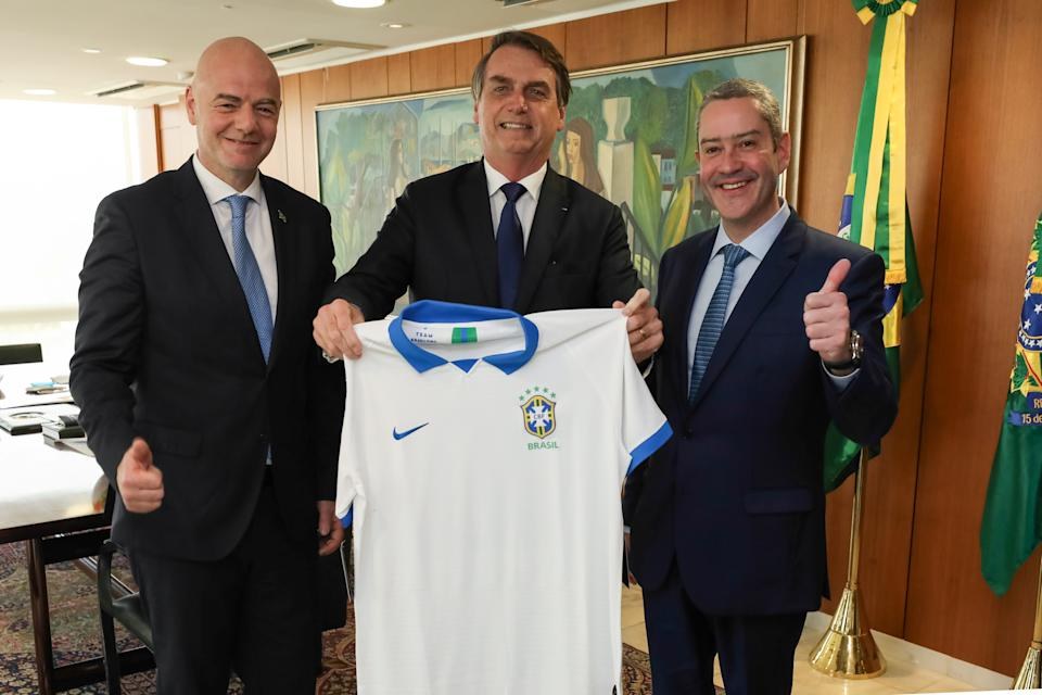 Brazil's President Jair Bolsonaro poses with Brazilian national soccer jersey between FIFA President Gianni Infantino and President of Brazilian Soccer Confederation Rogerio Langanke Caboclo at the Planalto Palace in Brasilia, Brazil April 10, 2019. Marcos Correa/Brazilian Presidency/Handout via REUTERS ATTENTION EDITORS - THIS IMAGE WAS PROVIDED BY A THIRD PARTY.