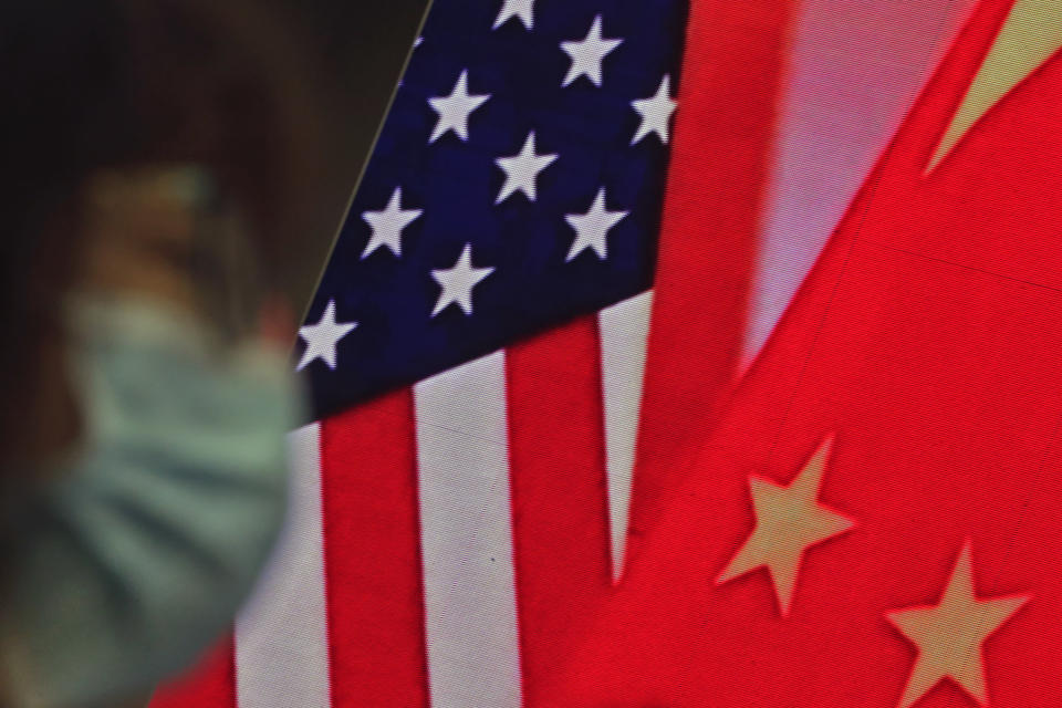 In this Feb. 22, 2021, file photo, a woman wearing a face mask sits near a screen showing China and U.S. flags as she listens to a speech by Chinese Foreign Minister Wang Yi at the Lanting Forum on bringing China-U.S. relations back to the right track, at the Ministry of Foreign Affairs office in Beijing. In a relationship as fraught as America's and China's, just an agreement that talks were productive was a sign of progress. Nine months into Joe Biden's presidency, the two sides finally appear to be trying to ease tensions that date from the Trump administration — though U.S. complaints about Chinese policies on trade, Taiwan and other issues are little diminished. (AP Photo/Andy Wong, File)