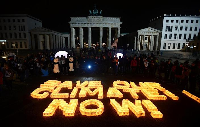 """Candles in paper bags are placed to form the lettering """"Save our climate, Now"""" in Berlin during the global climate change awareness campaign """"Earth Hour"""" on March 28, 2015 (AFP Photo/John Macdougall)"""