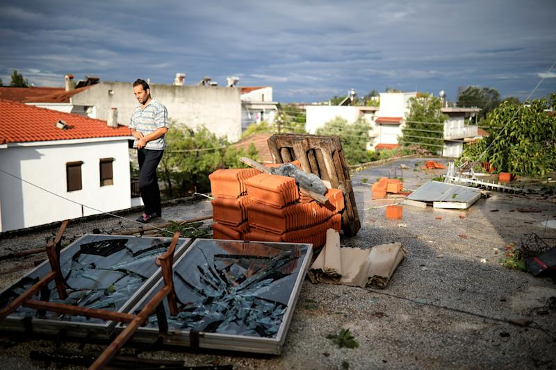 A man walks on a damaged terrace following heavy storms at the village of Nea Plagia, Greece, July 11, 2019. REUTERS/Alkis Konstantinidis - RC1F442EFA20