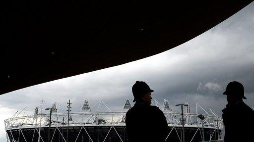 Metropolitan police officers look toward the Olympic Stadium from the entrance to the swimming venue in April 2012. British authorities insisted Thursday that Olympic security would not be compromised after having to draft in an extra 3,500 troops because a private security firm failed to provide enough guards