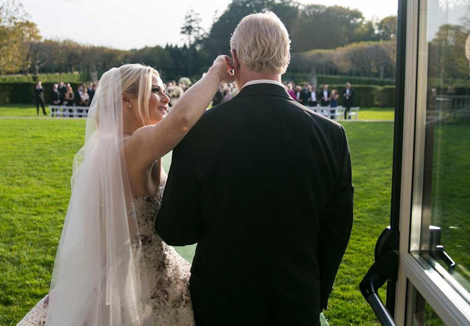 Just before their walk down the aisle, a photographer captures the moment Caroline Reuschel notices a white scar down the left side of her father's face.