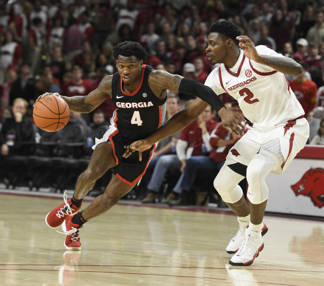 Georgia guard Tyree Crump (4) tries to get the ball past Arkansas defender Adrio Bailey (2) during the second half of an NCAA college basketball game, Tuesday, Jan.29, 2019 in Fayetteville, Ark. (AP Photo/Michael Woods)