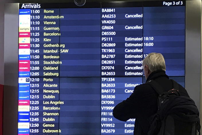 A passenger checks an arrivals board at Gatwick Airport in England, Friday, Dec. 21, 2018. Flights resumed at London's Gatwick Airport on Friday morning after drones sparked the shutdown of the airfield for more than 24 hours, leaving tens of thousands of passengers stranded or delayed during the busy holiday season.(AP Photo/Kirsty Wigglesworth)