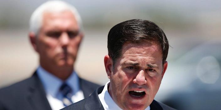 Arizona Gov. Doug Ducey, right, speaks as Vice President Mike Pence, left, watches after the two held a meeting to discuss the surge in coronavirus cases in Arizona Wednesday, July 1, 2020, in Phoenix.