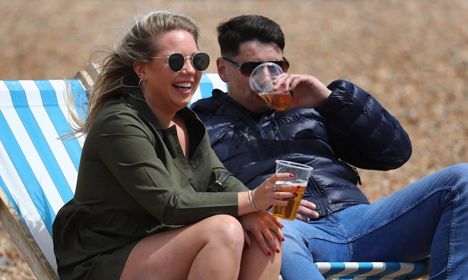 A young couple enjoy a beer in their deckchairs during the fine weather in Brighton, as people travel to parks and beaches with lockdown measures eased. (Photo by Gareth Fuller/PA Images via Getty Images)