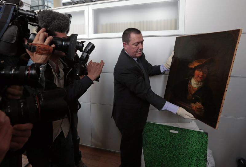 "Colonel Stephane Goffeni holds the painting ""L'enfant a la bulle de savon, 1630"" attributed to painter Rembrandt during a presentation to journalists at the court in Nice"