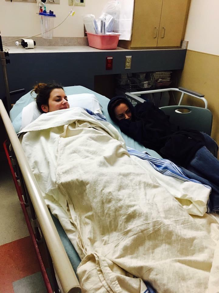 woman lying in a hospital bed covered with a blanket with her sister sitting next to her