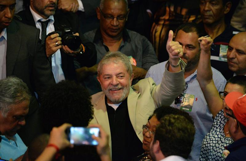 Brazilian former President Luiz Inácio Lula da Silva waves during a meeting with unionists and intellectuals in defense of state oil giant Petrobras, in Rio de Janeiro on February 24, 2015. Last week, Brazil's public prosecutor demanded that firms caught up in the huge kickbacks scandal at oil giant Petrobras pay some $1.5 billion in damages as well as yet-to-be-specified fines. AFP PHOTO/VANDERLEI ALMEIDA (Photo credit should read VANDERLEI ALMEIDA/AFP/Getty Images)